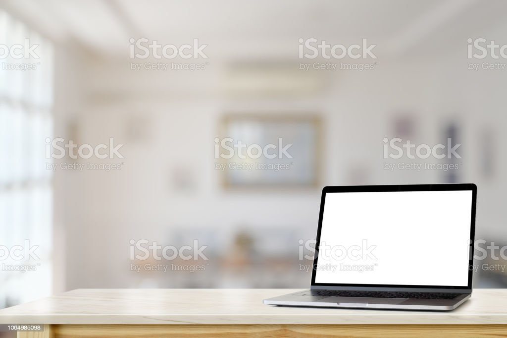 Mockup Blank screen laptop on table with living room background.