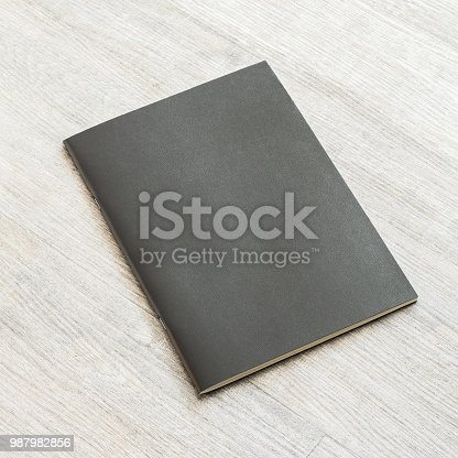 887572514istockphoto Mockup book with blank black leather cover template paper texture on wood table 987982856