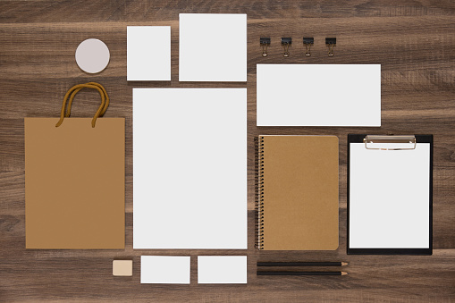 Mockup business template with shopping bag, notepads and envelopes. Natural wooden background.
