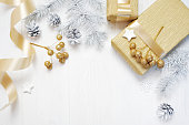 istock Mockup Christmas gift gold bow ribbon and tree cone, flatlay on a white wooden background, with place for your text 889521518