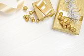 istock Mockup Christmas gift gold bow ribbon and tree cone, flatlay on a white wooden background, with place for your text 889521566
