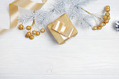 istock Mockup Christmas gift gold bow ribbon and tree cone, flatlay on a white wooden background, with place for your text 889521620