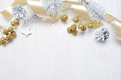 istock Mockup Christmas gift gold bow ribbon and tree cone, flatlay on a white wooden background, with place for your text 889521666