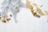 istock Mockup Christmas gold bow and tree cone, flatlay on a white wooden background, with place for your text 889524604