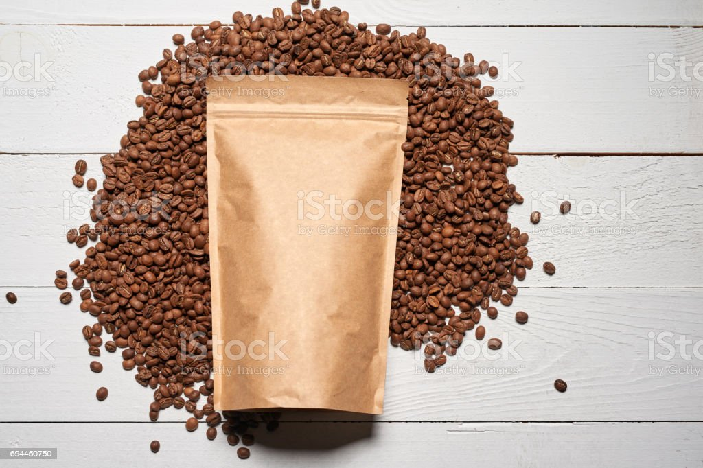 Mock-up craft paper pouch bags with coffee beans stock photo