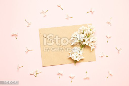 680461500 istock photo Mockup envelope with branches of lilac on a pink background 1152900372