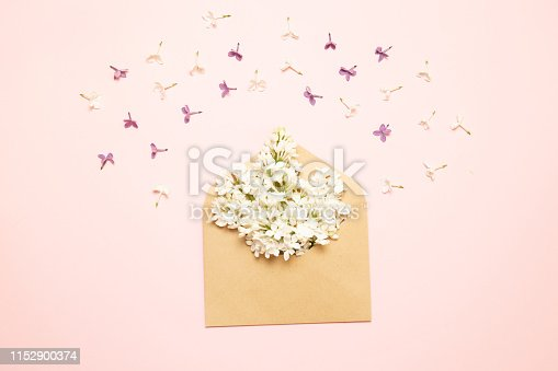 680461500 istock photo Mockup envelope with branches of lilac on a pink background 1152900374