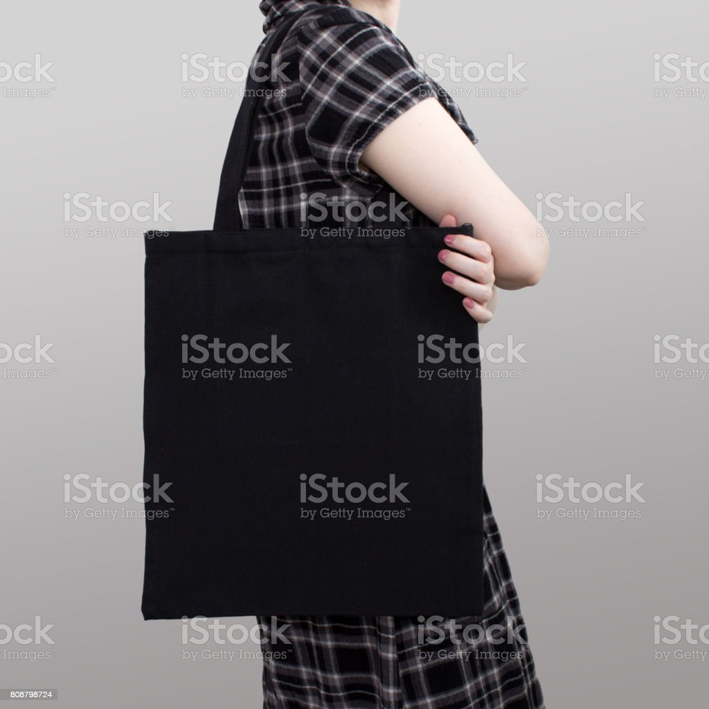 Mock-up. Girl in dress carries black cotton tote bag. stock photo