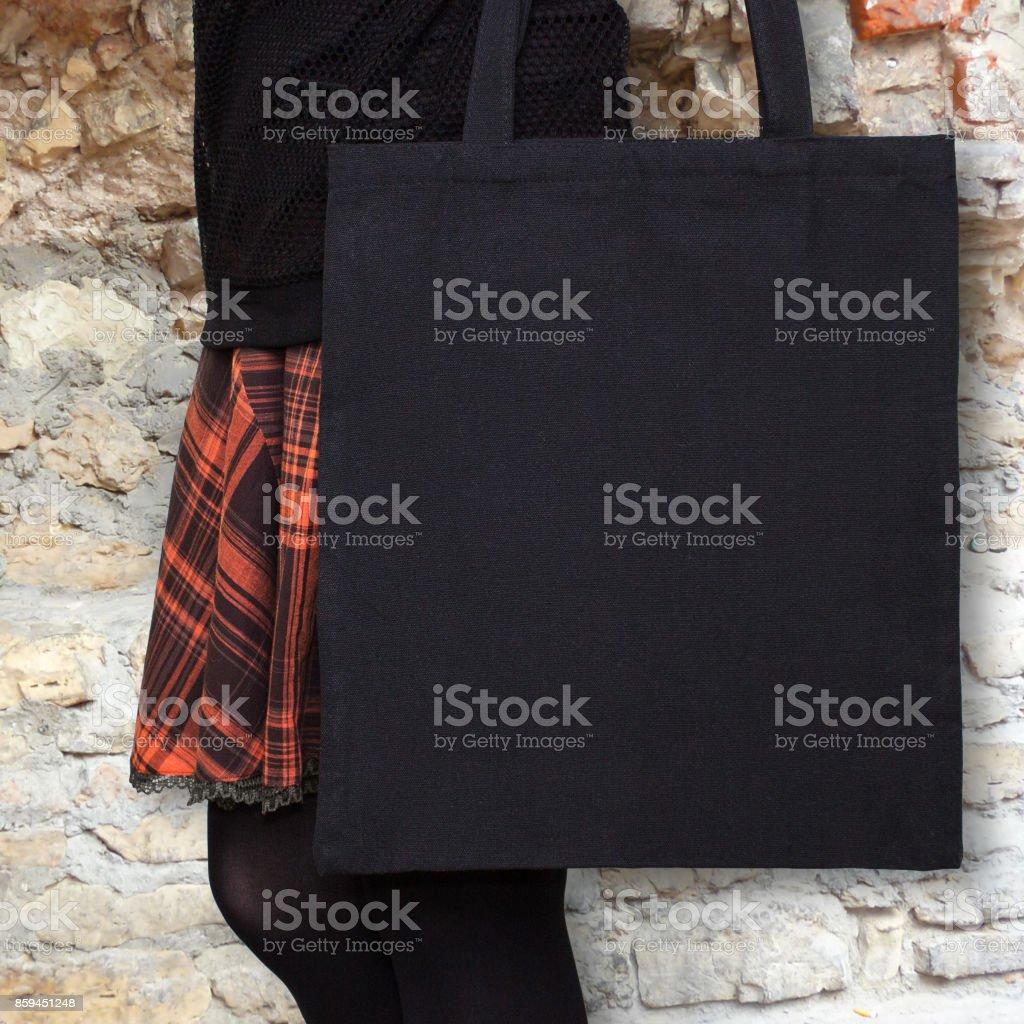 Maqueta. Chica en falda naranja tiene bolsa de algodón negro. Bolso de compras de eco a mano para las niñas. Maquetas de Halloween - foto de stock
