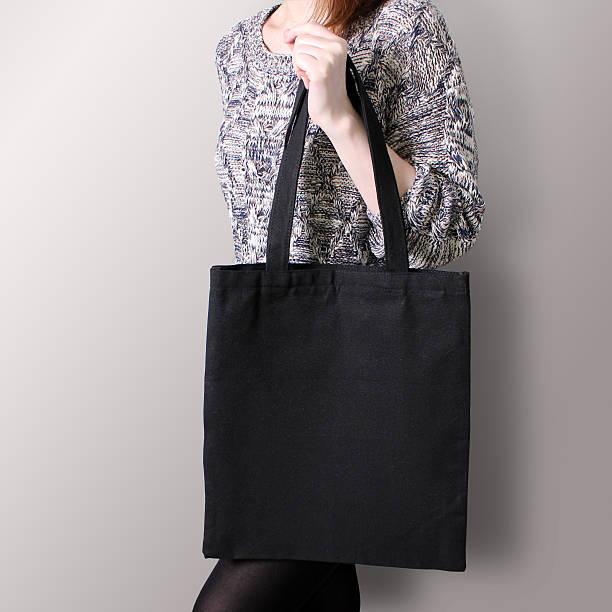 mock-up. girl is holding black cotton tote bag. - kinderhandtaschen stock-fotos und bilder