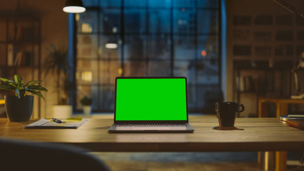 Mock-up Green Screen Laptop Standing on the Desk in the Modern Creative Office. In the Background Warm Evening Lighting and Open Space Studio with City Window View. stock photo