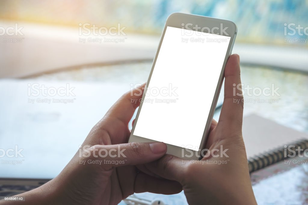 Mockup image of a hand holding and showing smart phone with blank white screen by swimming pool stock photo