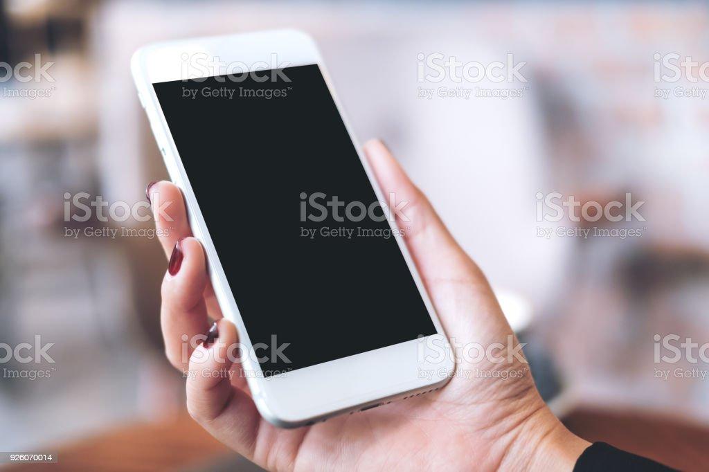Imagen de la maqueta de una mano sosteniendo blanco teléfono móvil con pantalla en blanco del escritorio negro con desenfoque de fondo - foto de stock