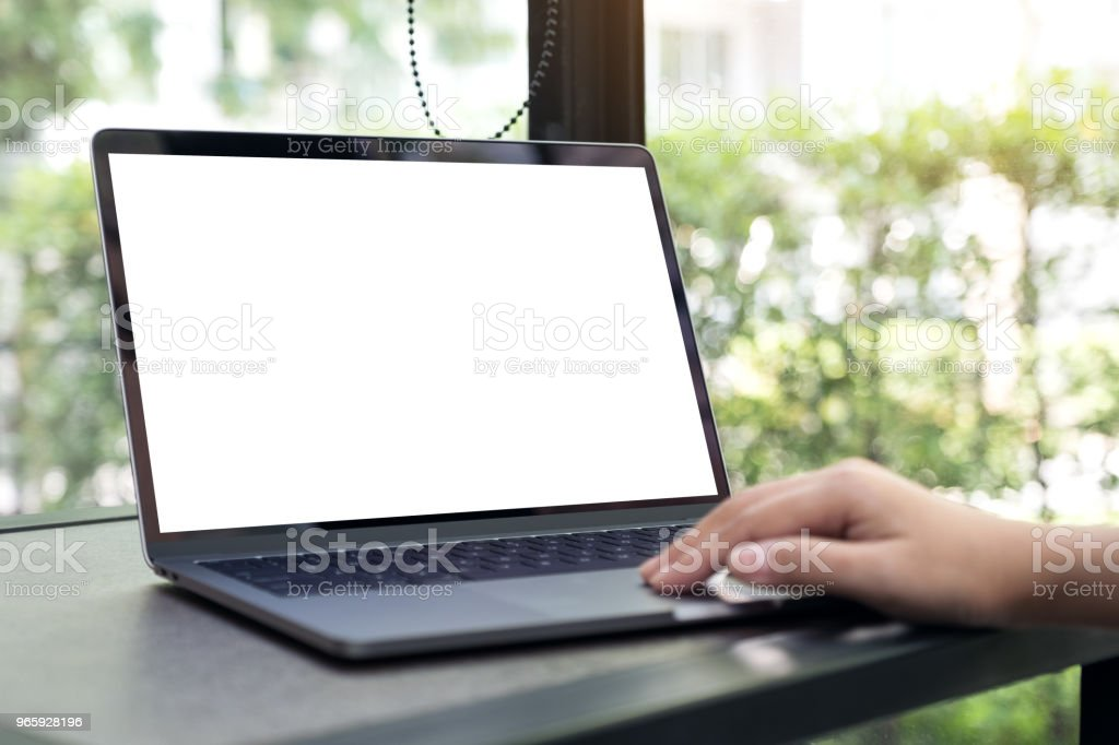 Mockup image of a hand using and typing on laptop with blank white desktop screen in cafe - Royalty-free Above Stock Photo