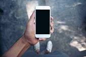 istock Mockup image of a man's hand holding white mobile phone with blank black screen while standing on concrete polishing floor 895945138