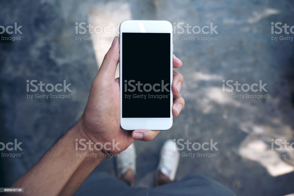 Mockup image of a man's hand holding white mobile phone with blank black screen while standing on concrete polishing floor stock photo
