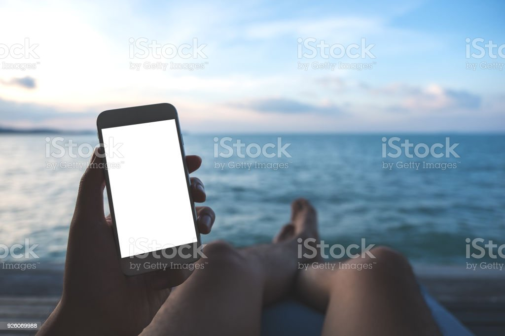 Mockup image of a man's hand holding white mobile phone with blank desktop screen sitting by the sea and blue sky background - foto stock