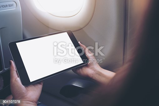 istock Mockup image of a woman holding and looking at black tablet pc with blank white desktop screen next to an airplane window with clouds and sky background 904107078