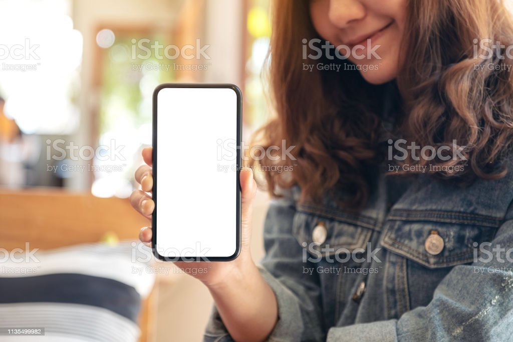Mockup image of a woman holding and showing black mobile phone with...