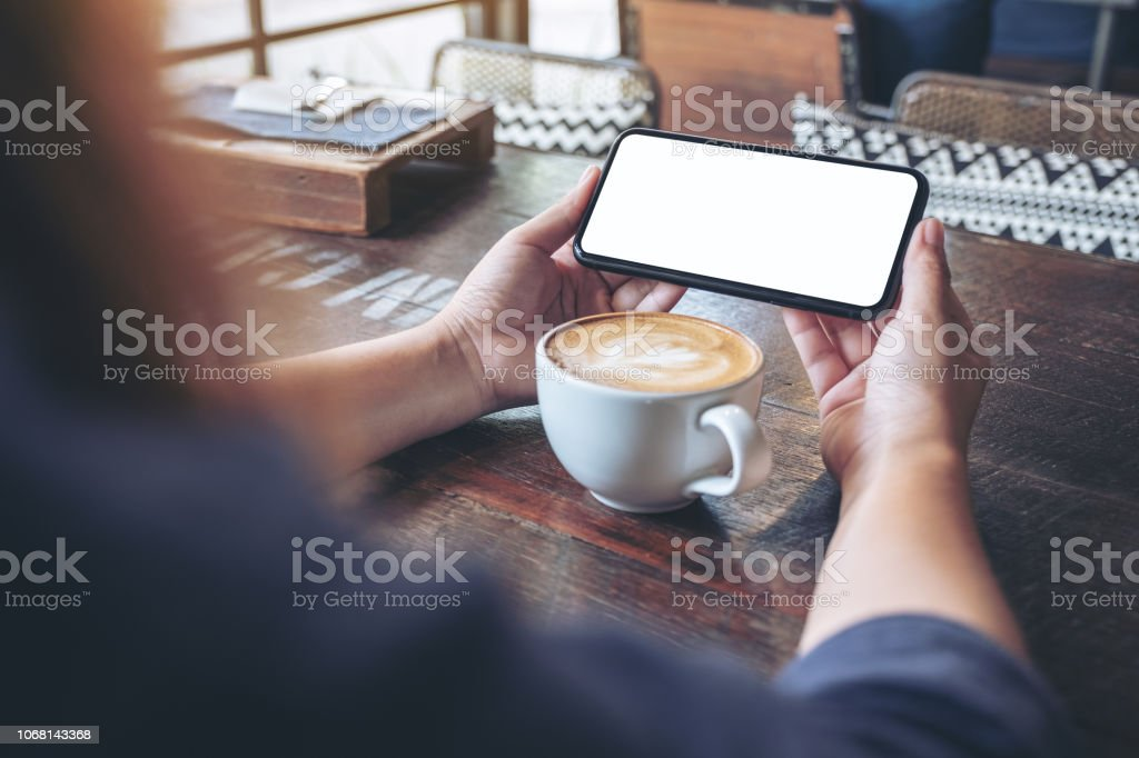 Mockup image of a woman holding and using a black mobile phone with...