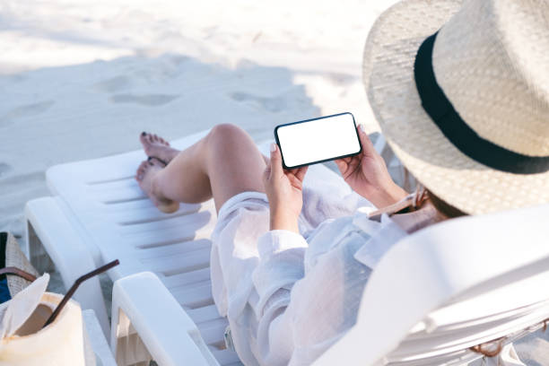 mockup image of a woman holding black mobile phone with blank desktop screen while laying down on beach chair on the beach - phone, travelling, copy space imagens e fotografias de stock