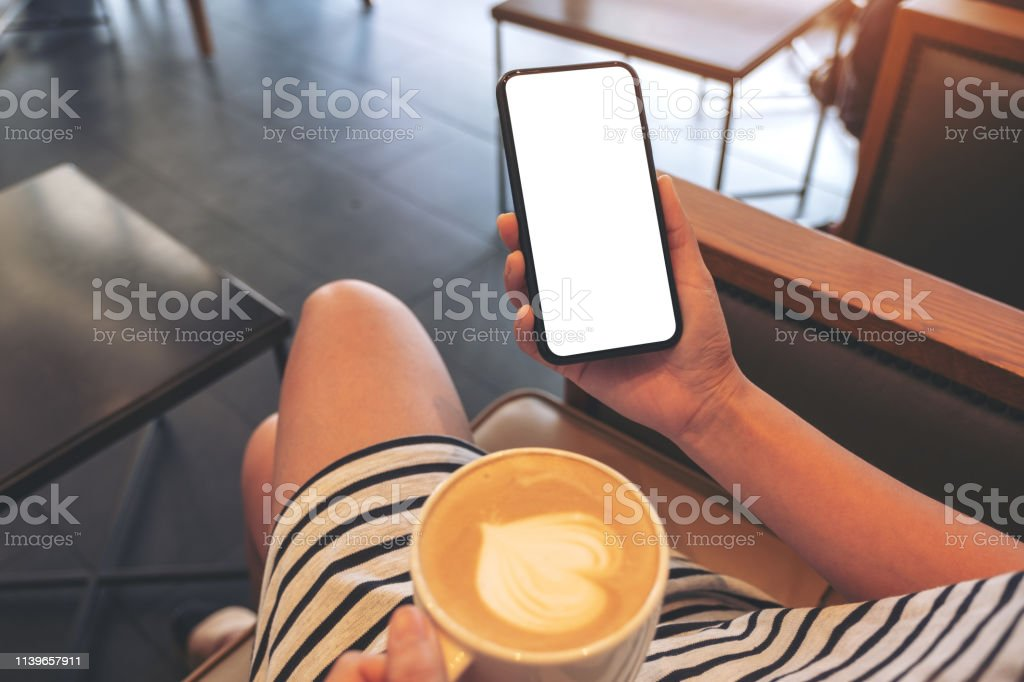 Mockup image of a woman holding black mobile phone with blank screen...