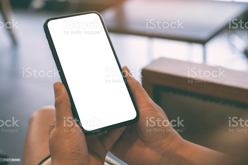 Mockup image of a woman holding black mobile phone with blank white...