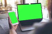 Mockup image of a woman holding blank mobile phone while using laptop with blank green screen on table