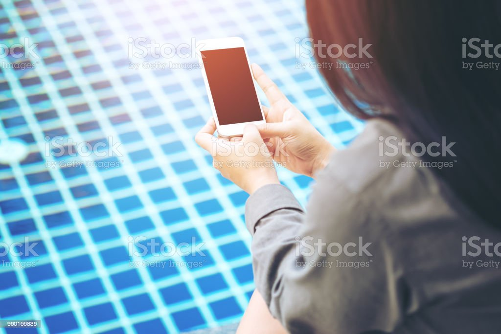 Mockup image of a woman showing smart phone with blank black screen by swimming pool stock photo