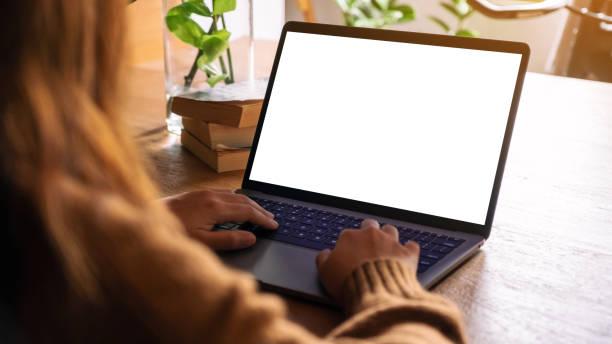 Mockup-Bild einer Frau mit und Eingabe auf Laptop mit leeren weißen Desktop-Bildschirm auf Holztisch – Foto