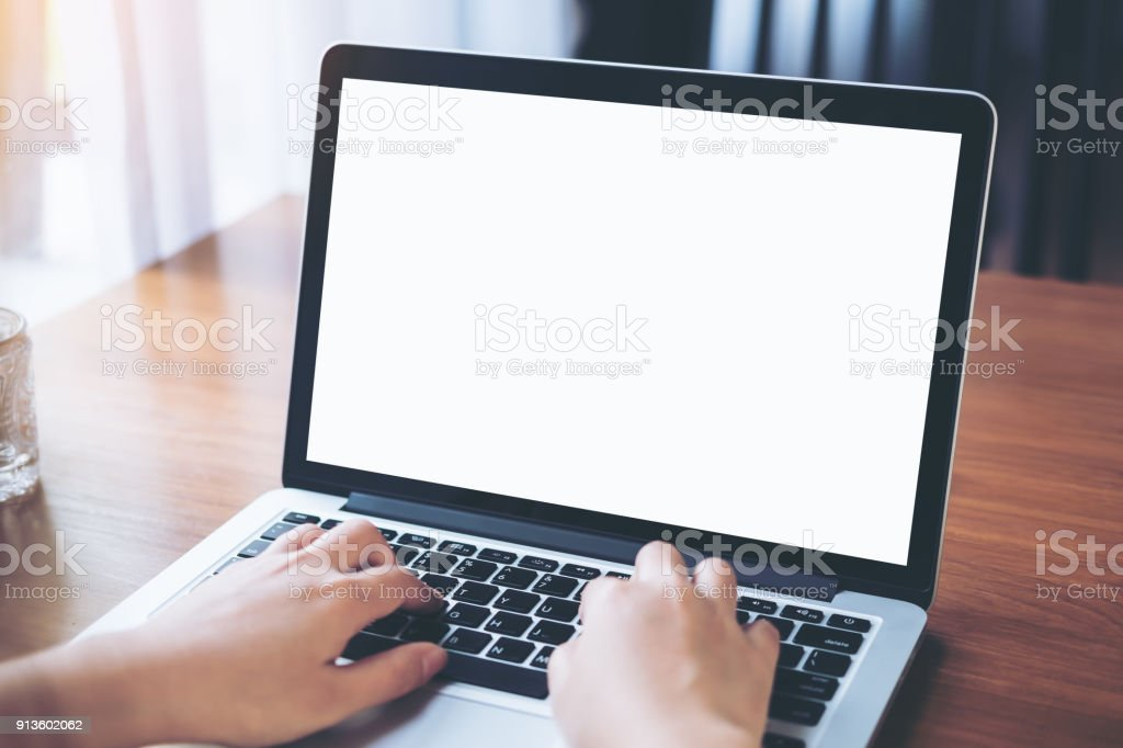 Mockup image of a woman using and typing on laptop with blank white screen on wooden table in modern cafe
