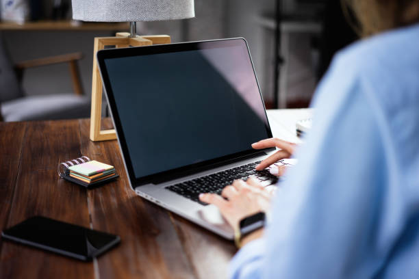 Mockup-Bild einer Frau mit Laptop mit leerem Bildschirm auf Holztisch – Foto