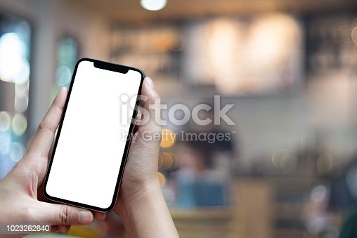 Mockup image of hand holding mobile phone with blank white Full screen in cafe For Graphic display montage.