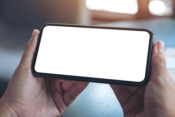 mock-up bild der hände halten schwarz handy mit leeren desktop-bildschirm horizontal - horizontal stock-fotos und bilder