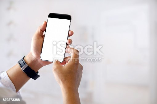 istock Mockup image of hands holding black mobile phone with blank white screen in office. 879573388