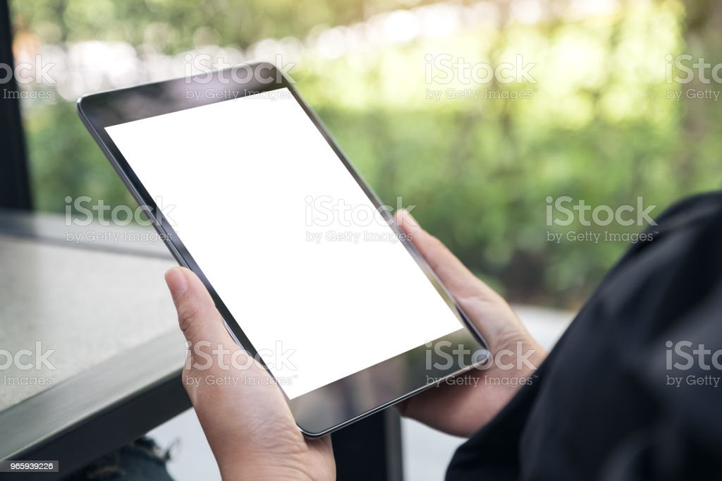 Mockup image of hands holding black tablet pc with blank white desktop screen on the table - Royalty-free Above Stock Photo