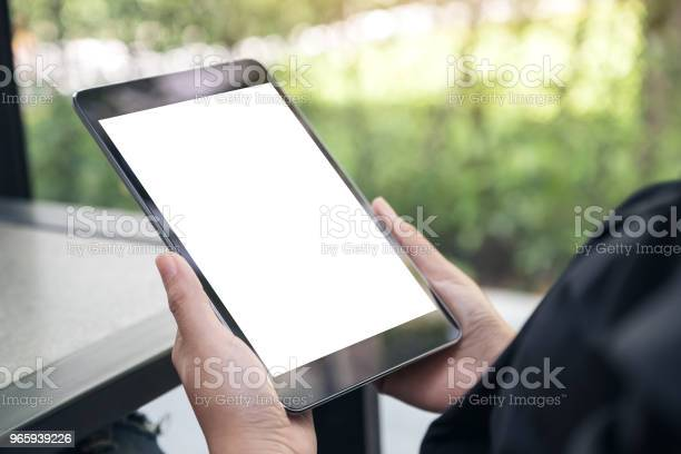 Mockup Image Of Hands Holding Black Tablet Pc With Blank White Desktop Screen On The Table Stock Photo - Download Image Now