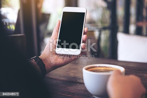 Mockup image of hands holding white mobile phone with blank black desktop screen and a coffee cup on wooden table in vintage cafe