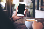 istock Mockup image of hands holding white mobile phone with blank black desktop screen and a coffee cup on wooden table in vintage cafe 940348572