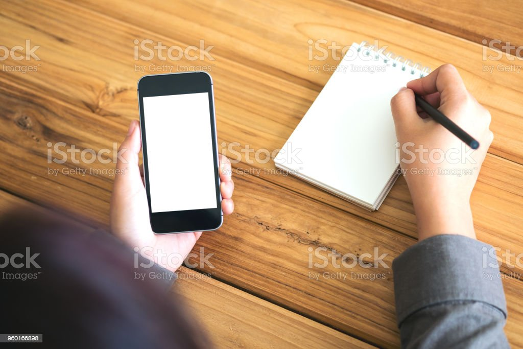 Mockup image of hands that writing on notebook and holding black...