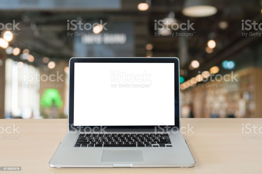 Mockup image of laptop with blank white screen on wooden table in modern library stock photo