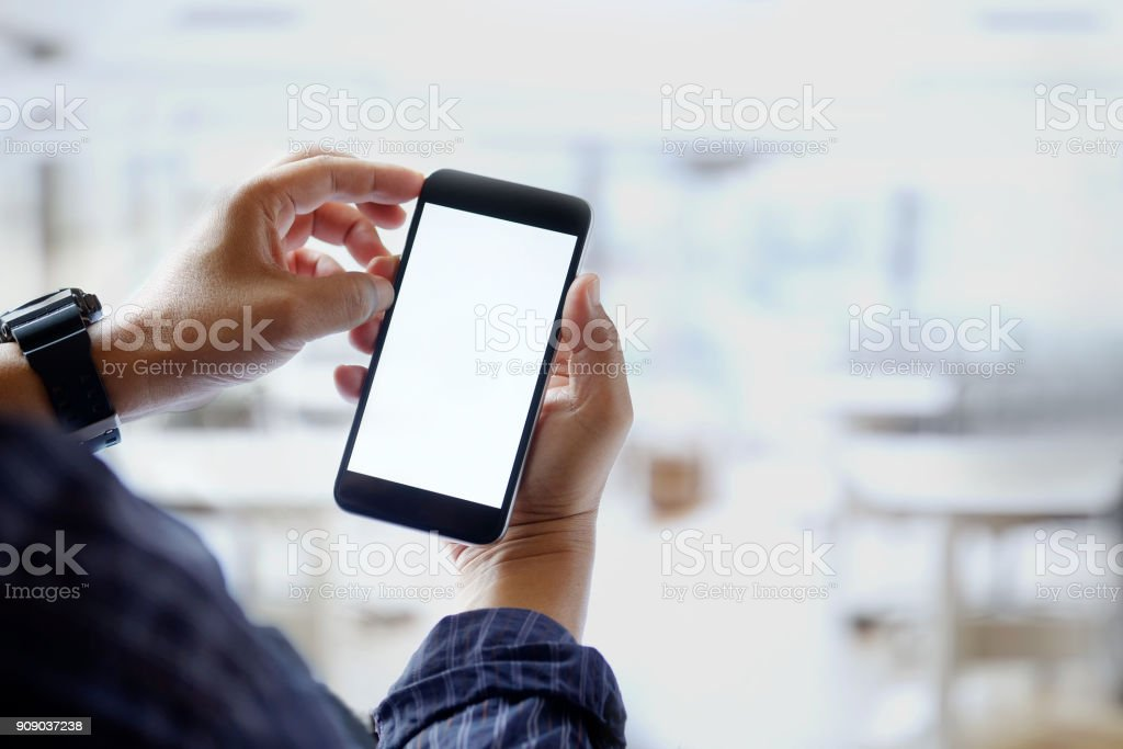 Mockup image of man hands holding black mobile phone with blank white screen in office. stock photo