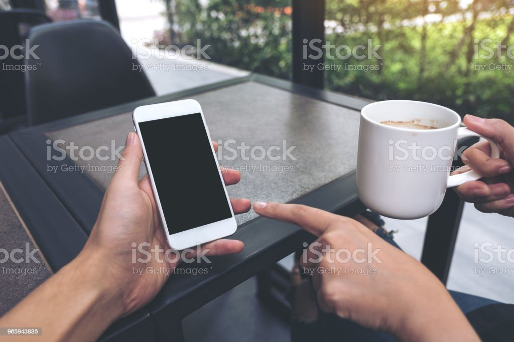 Mockup image of two people looking and pointing at a white mobile phone with blank black desktop screen in cafe - Royalty-free Above Stock Photo