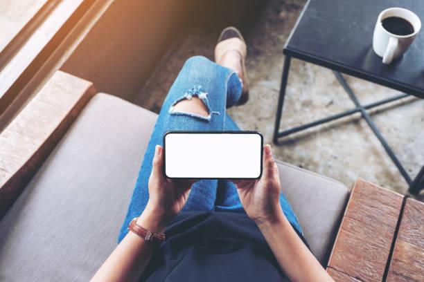 Mockup-Bild von Frau hält schwarzes Handy mit leerem Bildschirm – Foto