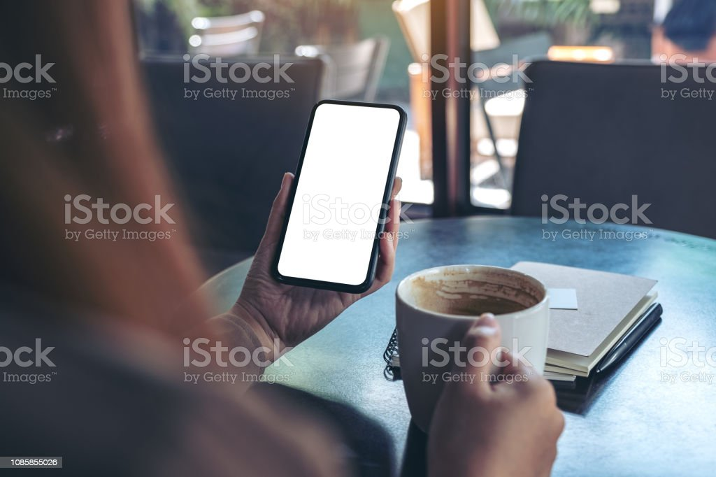 Mockup image of woman holding black mobile phone with blank white...
