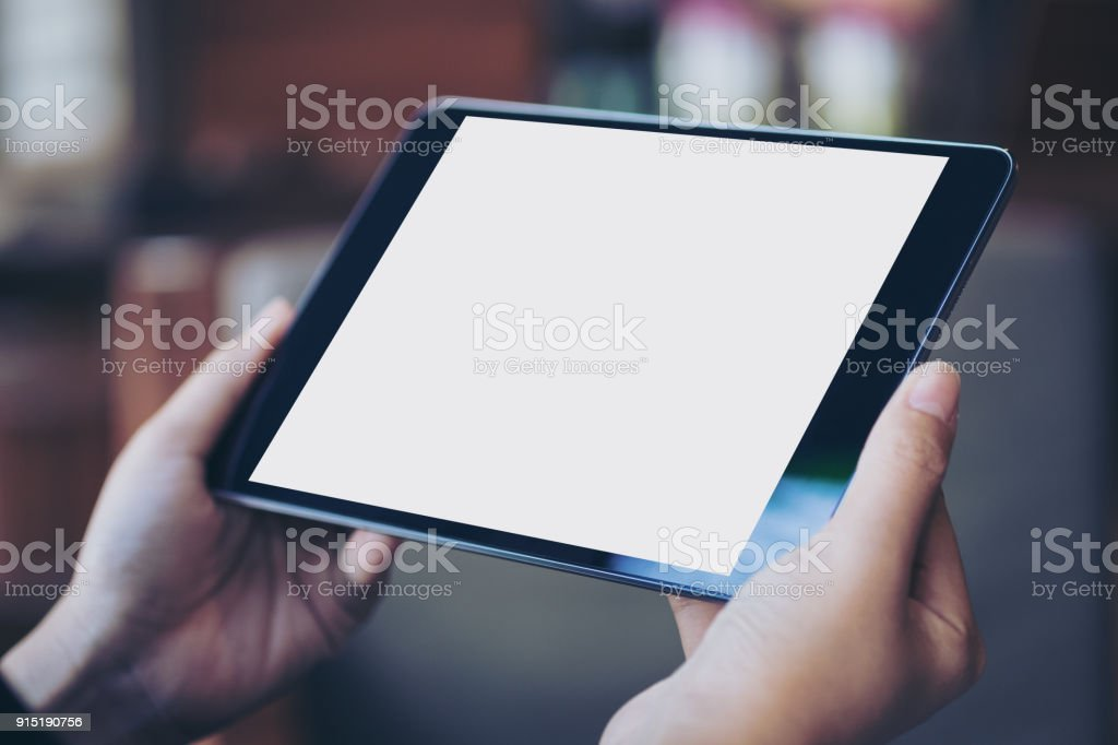 Mockup image of woman's hand holding black tablet pc with blank white screen in wooden cafe stock photo