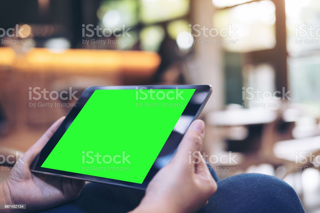 Mockup image of woman's hands holding black tablet pc with blank green screen on thigh with concrete floor background in modern cafe stock photo
