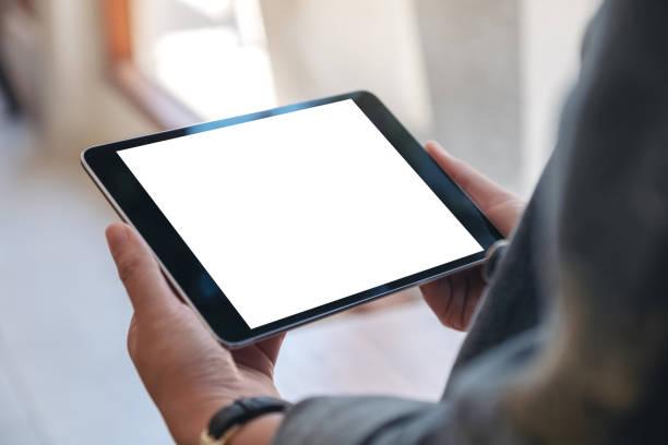 mockup image of woman's hands holding black tablet pc with blank screen horizontally in cafe - segurar imagens e fotografias de stock