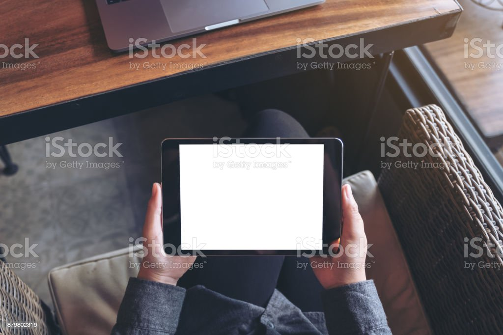 Mockup image of woman's hands holding black tablet pc with blank white screen on thigh with laptop in modern cafe stock photo