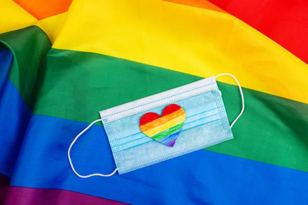 lgbtqプライドカラーのハートを持つlgbtプライドフラッグで作られたモックアップ。プライドデー2020とコロナウイルスcovid-19ロックダウンの検疫中の同性愛恐怖症に対する国際デー - lgbtqi  ストックフォトと画像